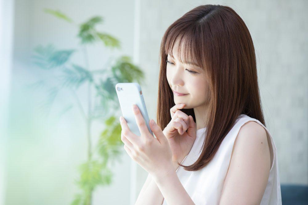 スマートフォンで調べ物をする女性
