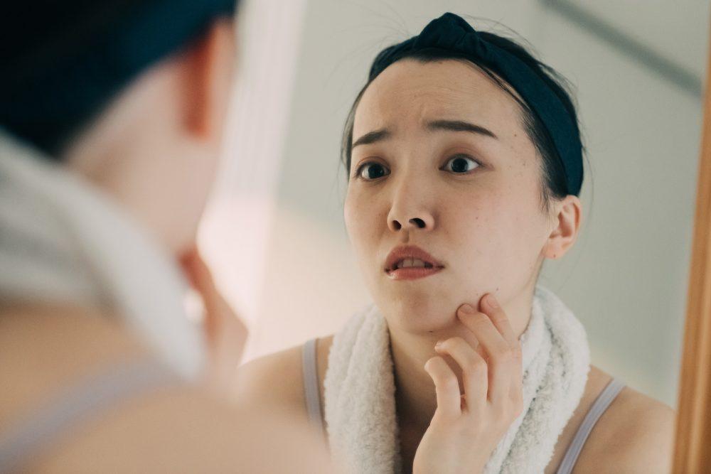 肌を心配して鏡をのぞく女性