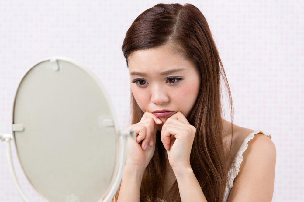 鏡を見てあごのラインを気にする女性