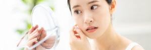 鏡で肌の調子をチェックする女性